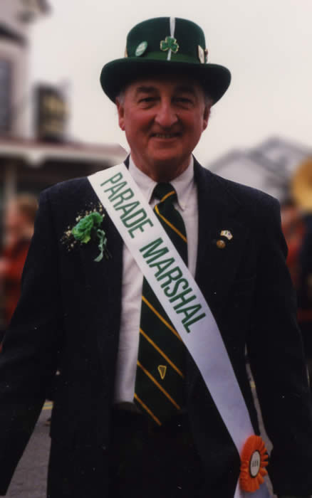 Picture of James Mahoney with Parade Marshal sash in front of Sig's